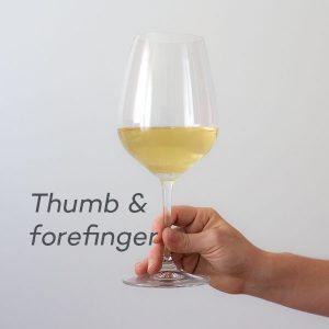 Ține piciorul paharului între degetul mare, arătător și degetul mijlociu care se pot odihni pe bază
